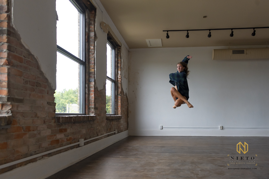dancer dressed in a plaid shirt dumping in the air with her legs tucked under her