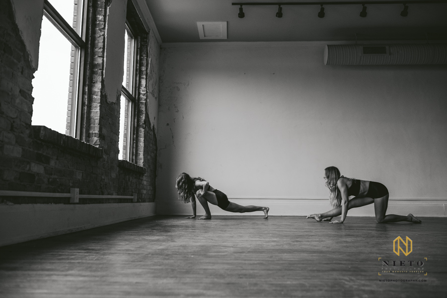 black and white image of two dancers stretching their legs on a hardwood floor