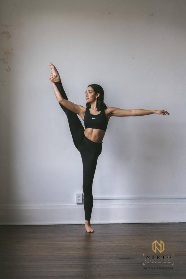 dancer stretching leg while dressed in Nike sports bra