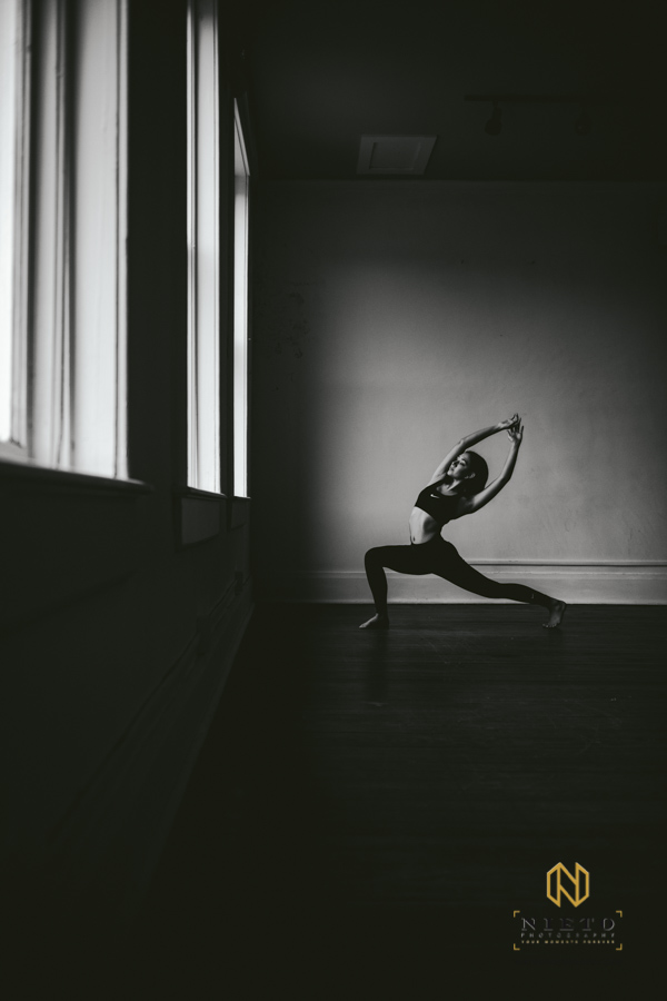 black and white image of a dancer in Nike sport wear stretching