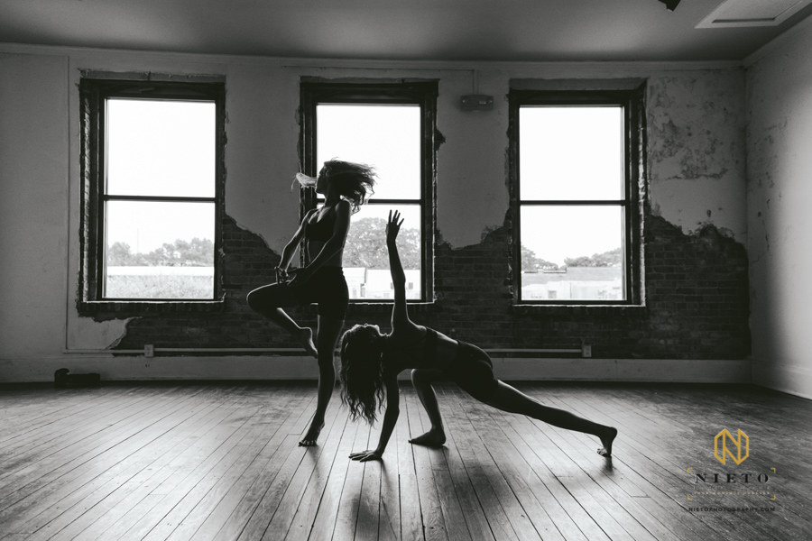 two dancers posing infant of three windows in a black and white image