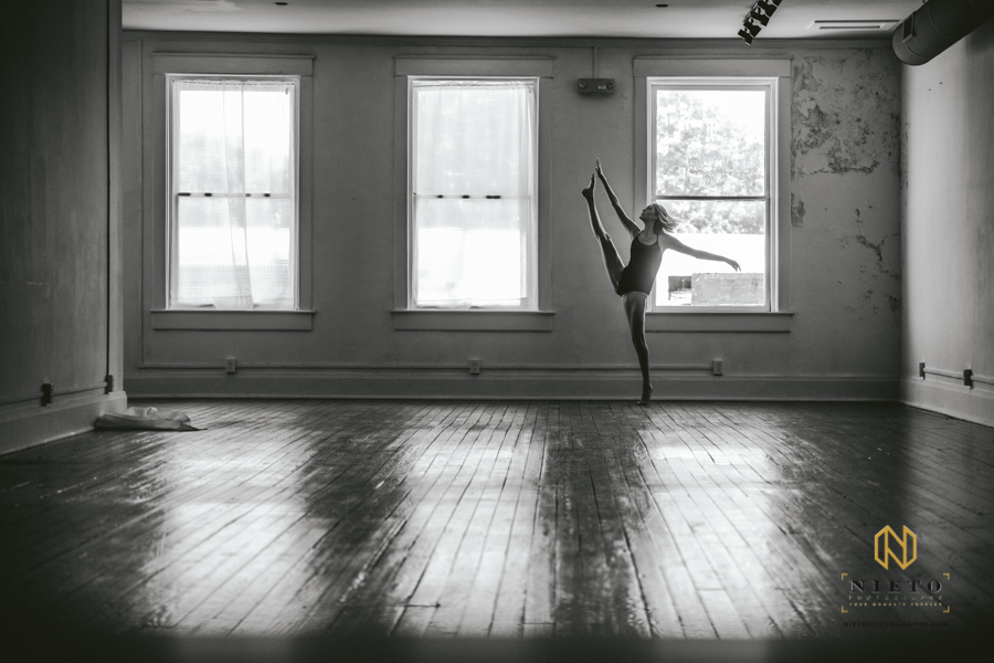 black and white image of a dancer in a leotard raising her leg into the air