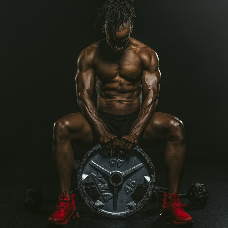 Fitness model holding and looking down at a 45 pound weight