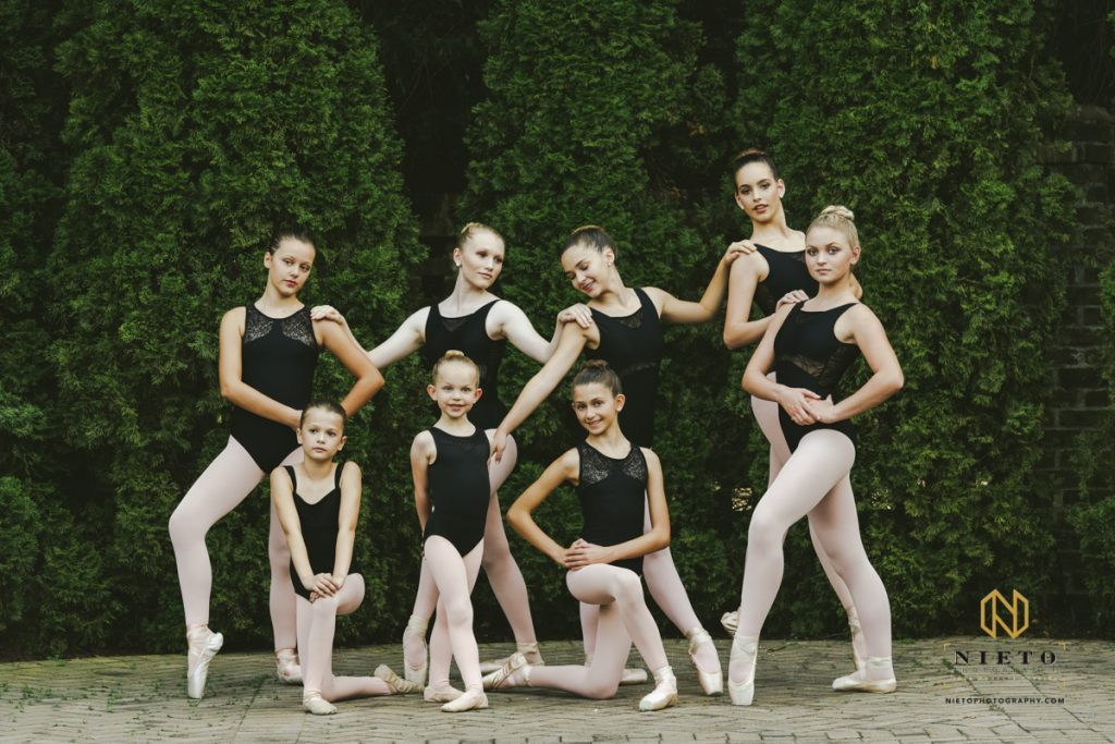 dancers in black leotards posing in a group against some green trees