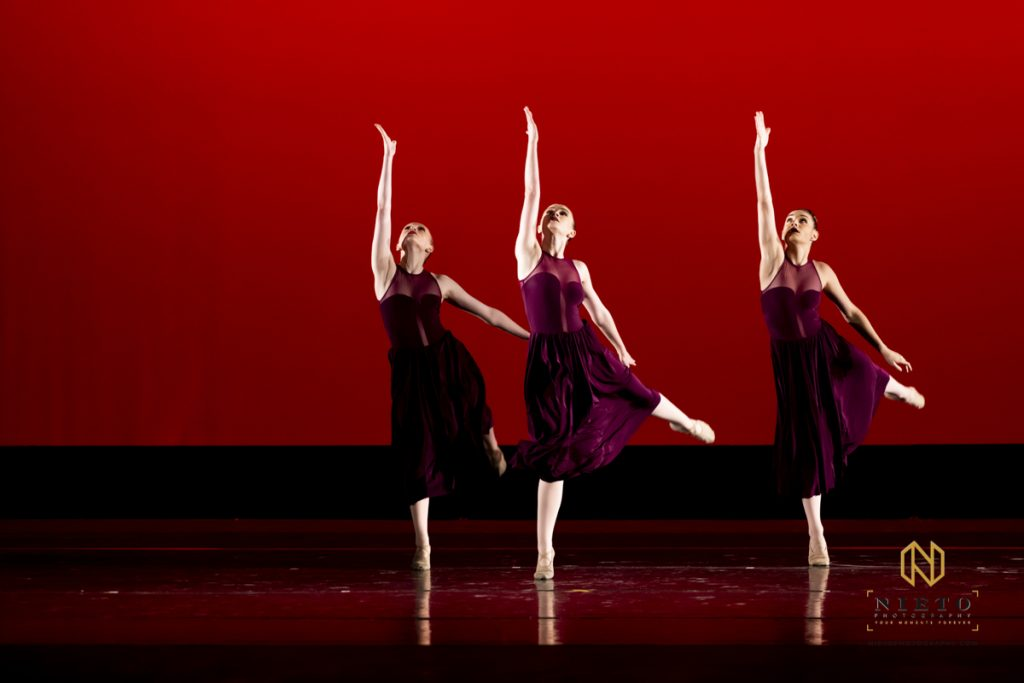 three dancers on a red back drop preforming a dance