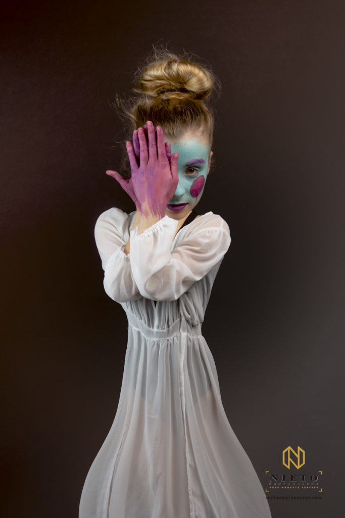 dancer in a white gown covering half her face with her purple face