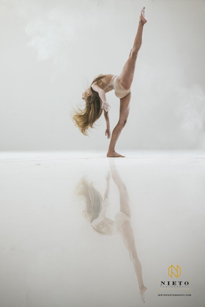 woman dancing with her reflection in the floor in a white room