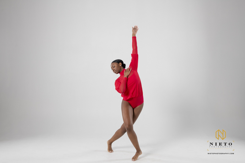 dancer in red outfit striking a pose against a white backdrop