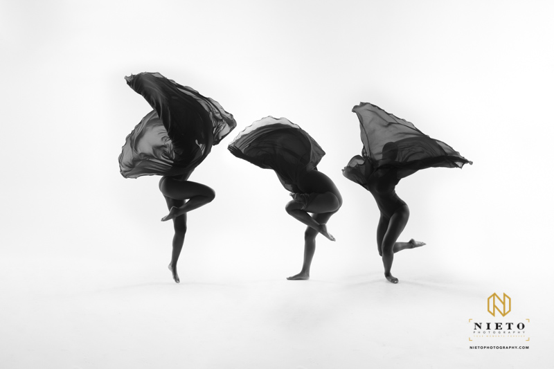 three dancers surrounded by cloth above their heads in a black and white image