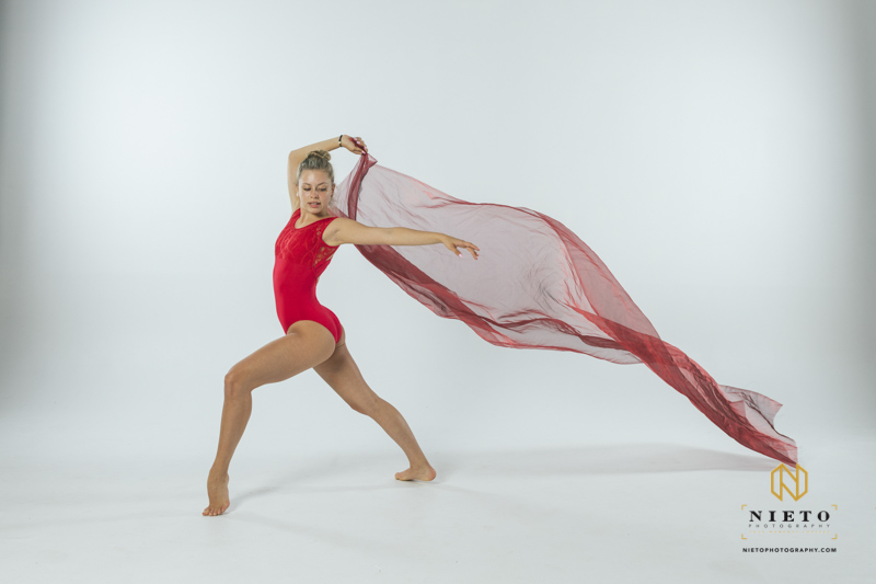 dancer in a red leotard posing while holding a red cloth