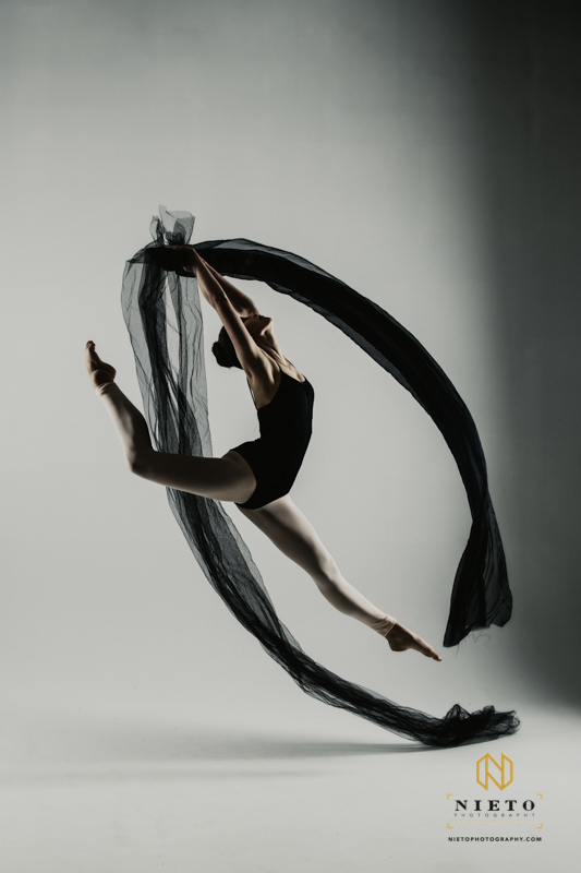 dancer jumping in a black leotard while holding a black cloth