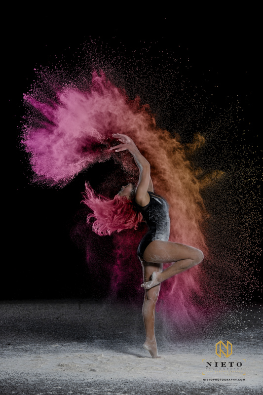 Dancer with pink hair throwing colored powder into the hair on a black background