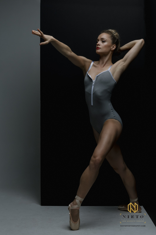 ballerina dancing in front of a black wall