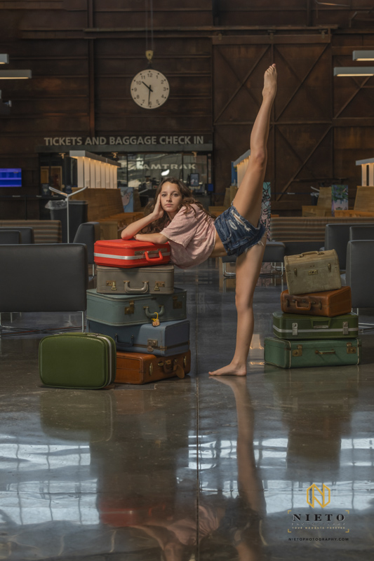 dancer in a train station posing for a portrait with her leg in the air